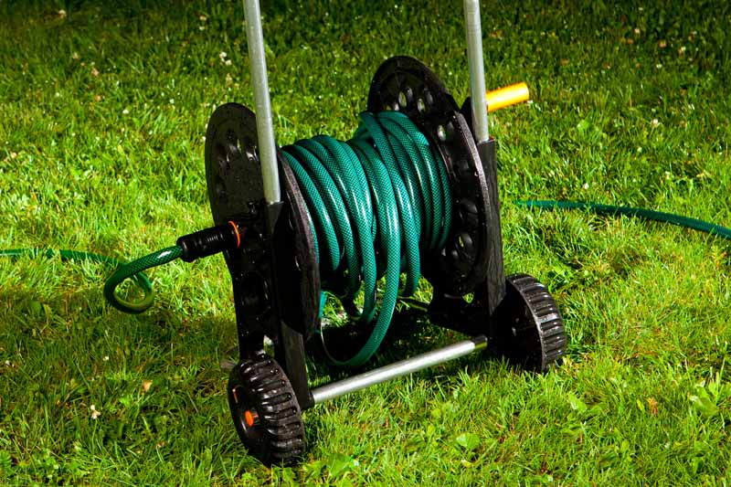 A mobile garden hose reel on wheels on green grass.