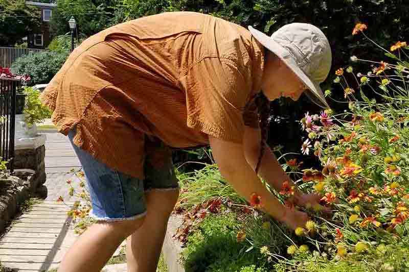 A woman weeding a garden, wearing a short sleeved sun protective blouse, and a wide brimmed hat with blue sky and trees in the background.