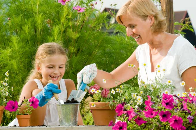 A mother and daughter work together to plant flowers in pots.