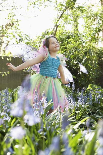 Cute young girl in fairy costume standing at flower garden
