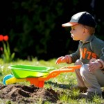 Little boy plays with toy garden tools.
