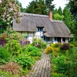 Cottage garden with center pathway leading to a rustic style tudor home with a thatched roof