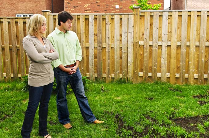 Atttractive Husband and wife stare ona bare patch in the grass in their backyard with concerned looks on their faces. Wooden fence in background.