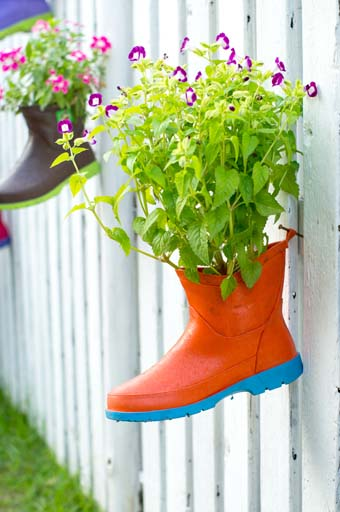 Two rain boots hund on whit picket fence and used as planters