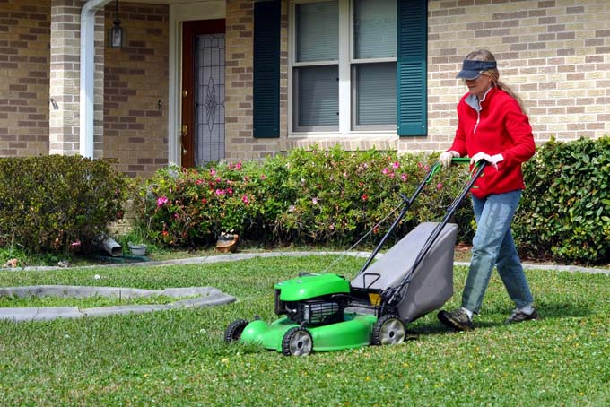 woman mowing lawn with push mower