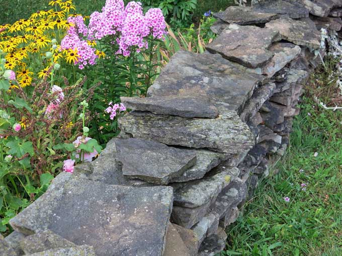 Stacked rock walls work well to contain overflow and reduce maintenance | Gardenerspath.com
