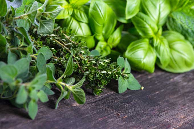 A close up of a variety of freshly cut herbs set on a wooden surface.
