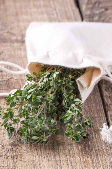 A close up of a small bunch of freshly harvested thyme in a white bag, set on a wooden surface.