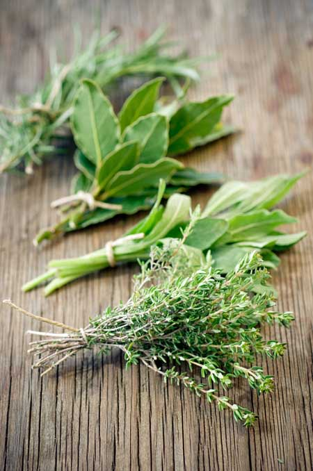 A vertical picture of four small bunches of herbs, their stems tied together, set on a wooden surface.