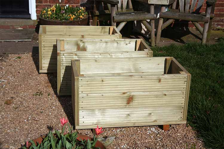 A set of three above-ground planters made from decking timber pictured in bright sunshine.