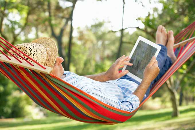 A man lying in a multicolored hammock reading a tablet with a garden scene in soft focus in the background.