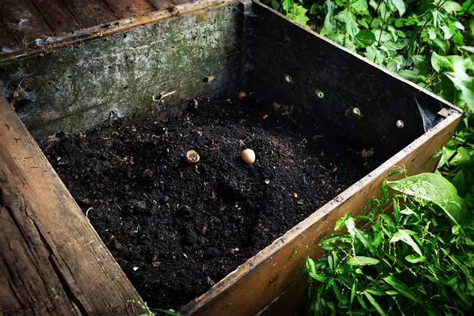 A large wooden vermicompost container set in the garden, half filled with dark, rich soil.