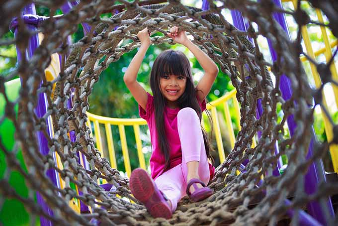 Girl in Rope Playground Tunnel | GardenersPath.com