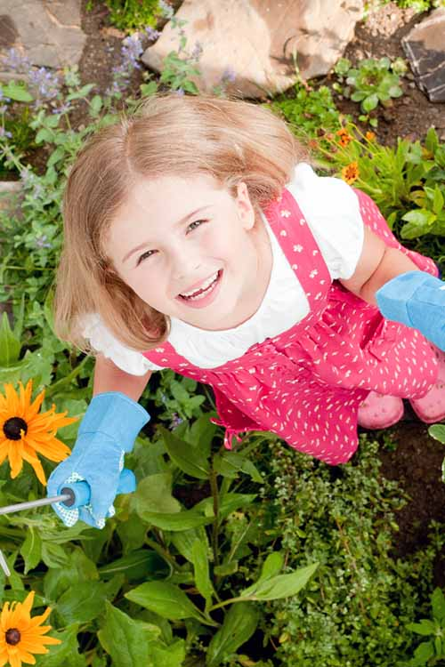 A close up top down picture of a child laughing in the garden after planting out seedlings.