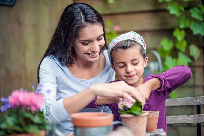 Woman and Daughter Potting Plants | GardenersPath.com