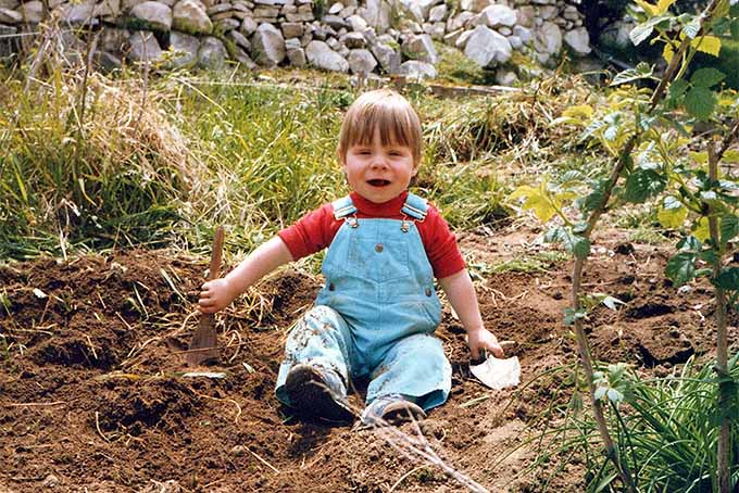 A small boy with blonde hair in a red t-shirt and blue overalls sits in the garden, between plants and seated on brown soil.