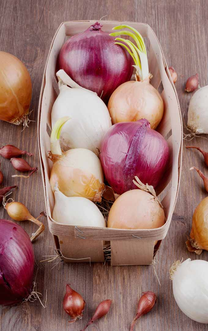 A wooden crate full of different colors of onion bulbs.