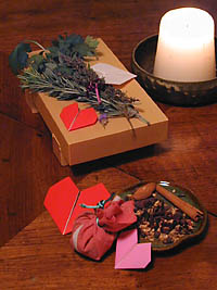 Lover's charm made with parsley, sage, rosemary, and thyme, beside a candle and a small dish of dried spices.