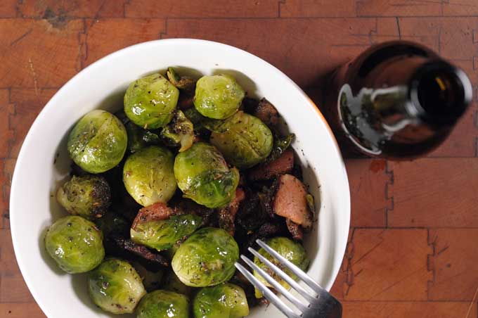 Top down view of sauteed Brussels sprouts with bacon and dill in a white porcelain bowl sitting on dark maple cutting board.