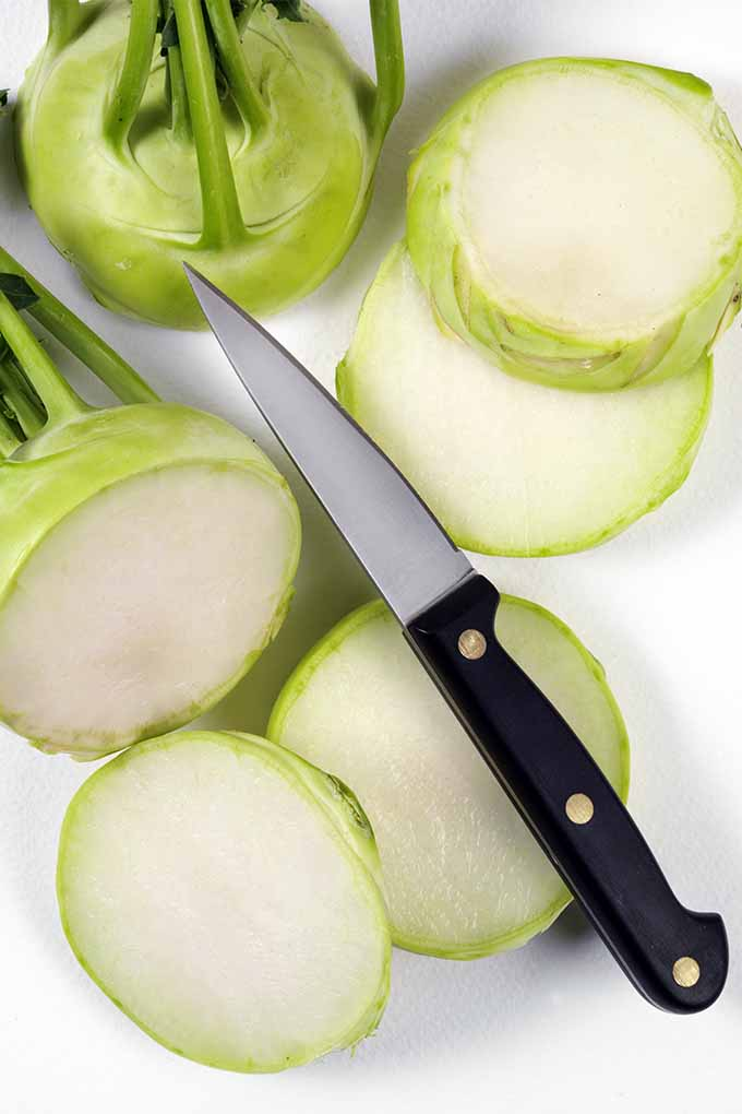 A yellow-green kohlrabi is shown sliced on a cutting board, accompanied by a paring knife and an upright whole kohlrabi.