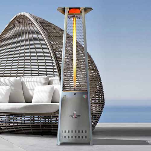 Italia Lite stainless steel patio heater, on a cement surface with a wicker nest-style chair in the background with white cushions and pillows, and a sky blue gradient background.