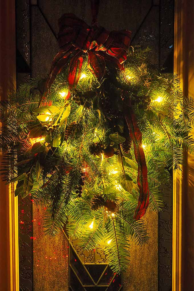 Add our simple tutorial to your holiday decorating plans- we'll teach you how to make an evergreen holiday swag to hang on the front door: https://gardenerspath.com/how-to/design/diy-holiday-swag/ #curbappeal #Christmas #holidaydecorating #evergreen #pine #tiedwithribbon