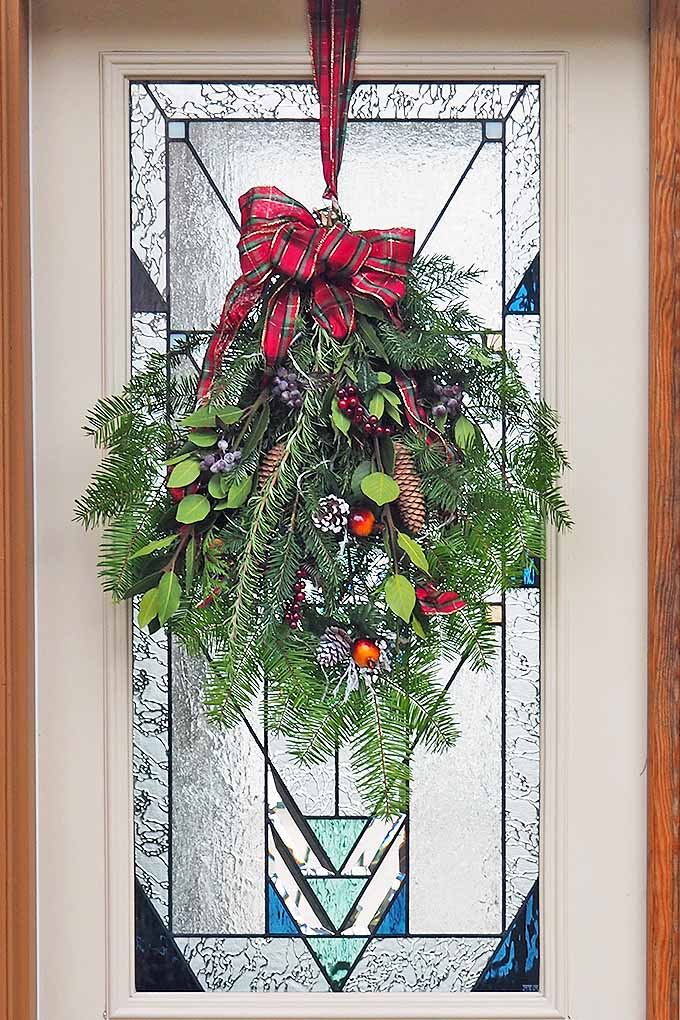 Too busy to make a complicated wreath? Learn how to make your own evergreen holiday swag with our tutorial: https://gardenerspath.com/how-to/design/diy-holiday-swag/ #Christmas #decorations #evergreen #gardening #holly #pinecones