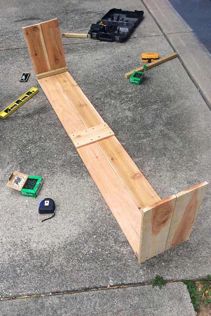 Vertical image of half of the frame for a wooden garden planter, resting on its side on a blacktop driveway next to a yellow level, a tape measure, a box of screws, a black box, and other assorted tools.