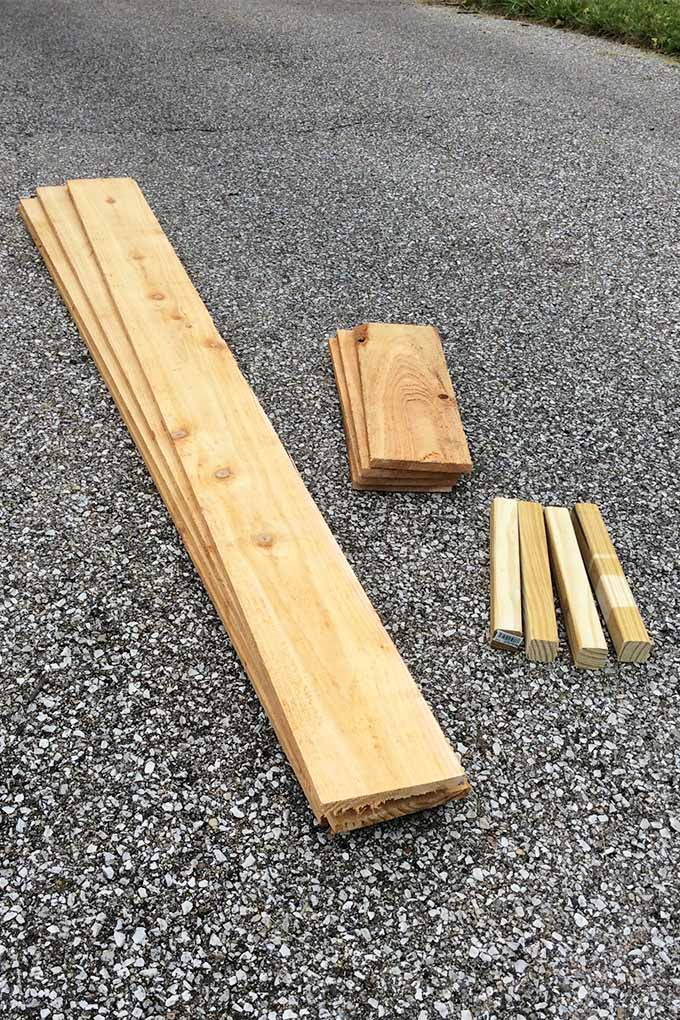 Several pieces of lumber of various sizes, resting in piles arranged according to size on a blacktop driveway.