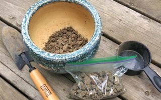 A small handheld spade sits on a rough wooden table next to a ceramic pot and a bag both containing samples of dirt. The soil in them is dry and clumped together. To the right of them all is a small, black measuring cup.