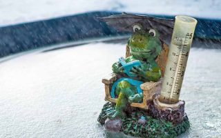 A decorative rain gauge with a clear canister that is almost full of water, market with measurements in inches and centimeters, with a green resin frog sitting in a brown Adirondack chair and reading a blue book beneath a pink umbrella, set on a cement surface with rain gently falling on a cloudy day.