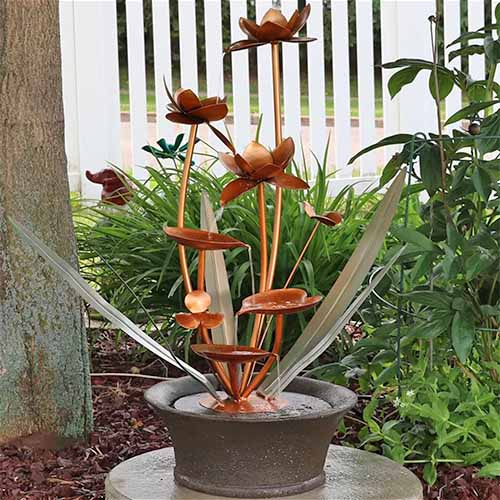 Fiberglass and copper flower blossoms decorative garden fountain, in a garden bed topped with wood mulch, with green plants and a white fence in the background, beside a beige stucco wall.