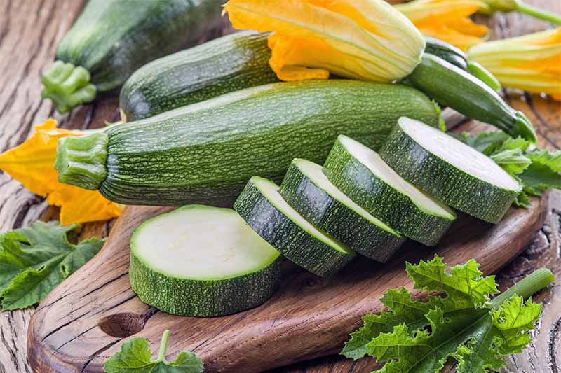Whole and sliced green zucchini with orange squash blossoms on a small wooden cutting board surrounded by a few leaves, on a brown wood surface.