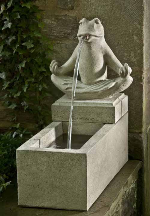 A concrete water fountain which include a frog spitting water into a trough.