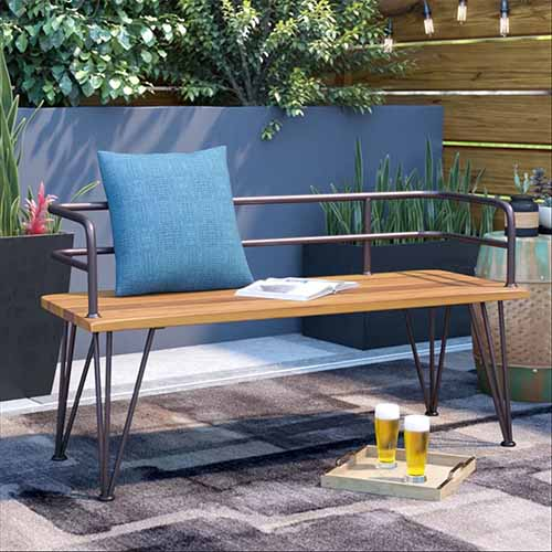 Guyapi metal and brown wood garden bench with modern look and triangular legs, on a patio with two glasses of beer, and potted plants in the background.