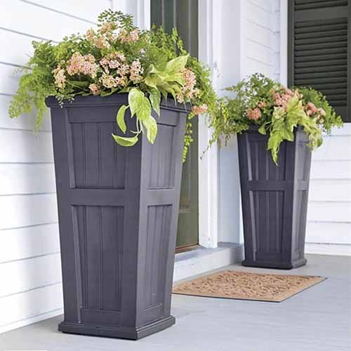 Tall square Lexington planters on either side of a green font door, on a gray patio with a tan door mat in between them, and white siding on the building.