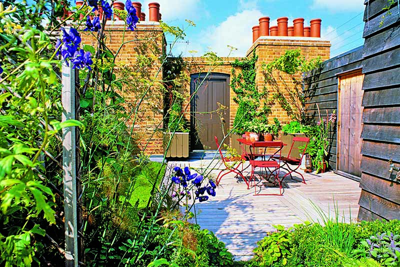 A rooftop deck with a table and chairs, and various plants growing around the border, with a brick chimney topped with red chimney pots, and a blue sky in the background.