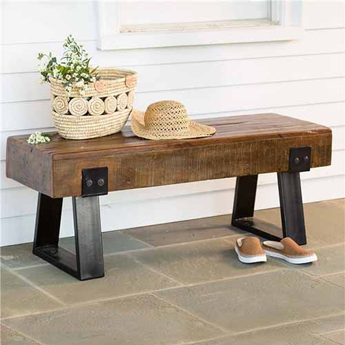 Brown wood and metal reclaimed wood bench, with a wicker basket and hat on top, and a pair of slip-on sneakers on the tile floor in front of it.