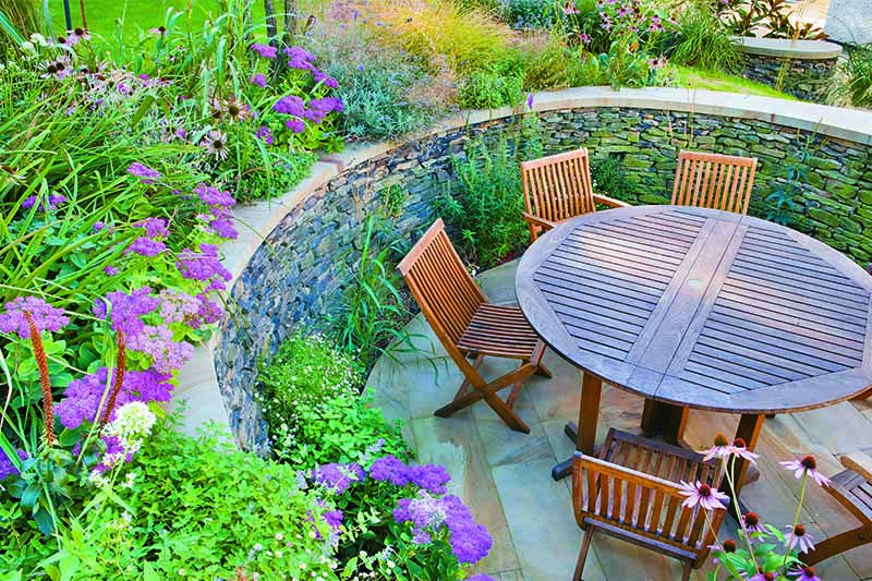 Circular seating area, retaining dry-stone wall, table and chairs.