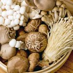 A round bamboo steamer basket is filled with a selection of five different type of brown andwhite mushrooms, including enoki, crimini, and oyster, on a brown wood background.