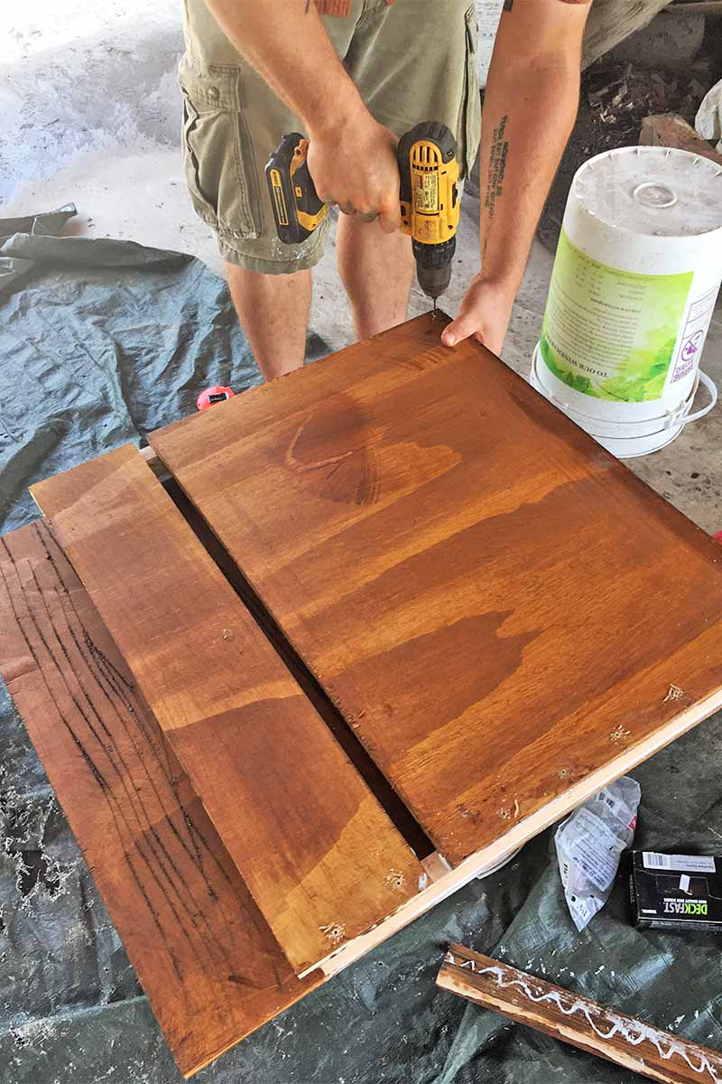 A man in tan cargo shorts drills screws into a homemade bat box, on a black tarp in a garage with scattered tools and materials on the cement floor.
