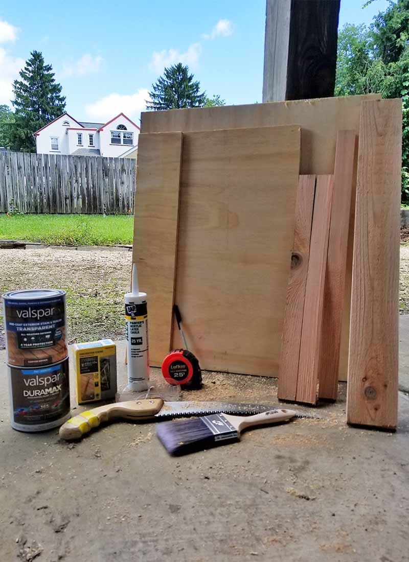 Vertical image of several pieces of wood of various sizes, stain, paint, caulk, a hand saw, a tape measure, and a paint brush, on a cement patio with a house, trees, blue sky, wood fence, and green lawn in the background.