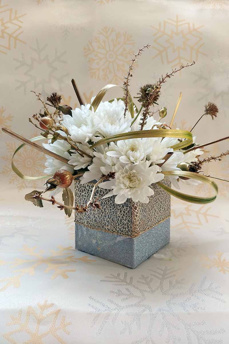 White mums and garden greenery arranged in a square silver container wrapped with decorate ribbon, on an off-white background.