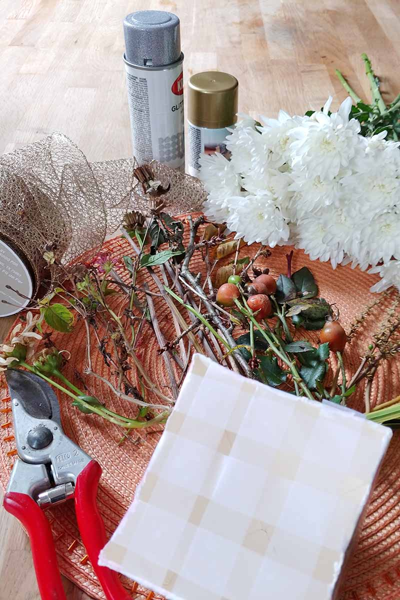 A collection of supplies used to make a flower arrangement including foliage gathered from the garden, white chrysanthemums, a roll of gold wired ribbon, cans of metallic spray paint, red and silver pruners, and a cardboard carton topped with a Scotch tape grid, on a melon-colored place mat.