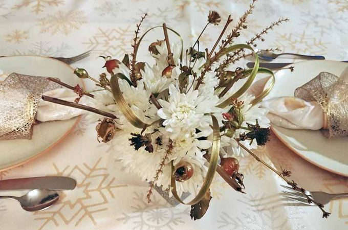 Overhead shot of a centerpiece comprised of white chrysanthemums, grasses, rose hips, and twigs from the garden, at the center of a table set with two white and orange plates with cream-colored cloth napkins tied with gold ribbon on top, with silverware at each place setting, on a cream-colored tablecloth with a gold and silver snowflake pattern.