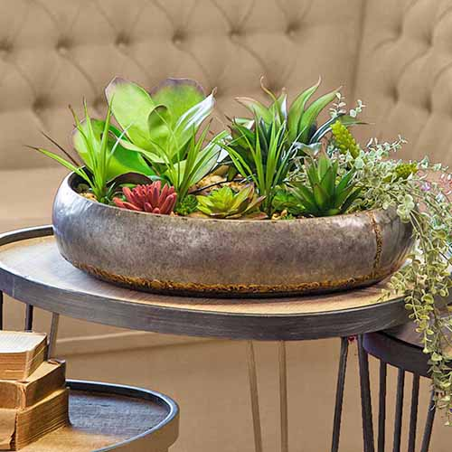 Square image of succulents growing in a shallow, round, metal container on a lightweight table, with two more nesting tables to the left and right, and a beige banquette in the background.
