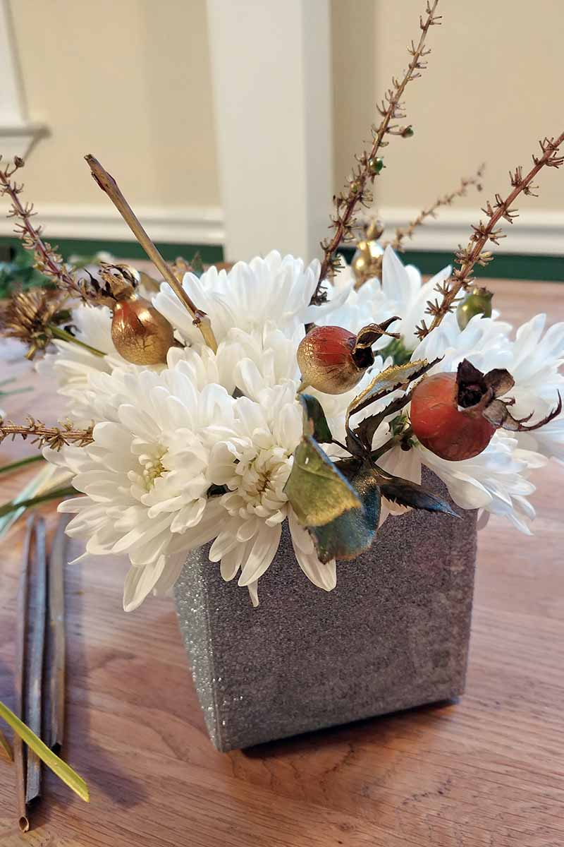 White mums, rose hips, and garden foliage arranged in a square silver container, on a beige surface with twigs from the garden to the left, against a beige, white, and green background.