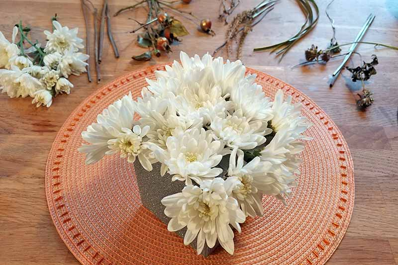 White mums in a square container on a round melon-colored place mat, on a brown wood surface surrounded by cut flowers and assorted garden greenery.