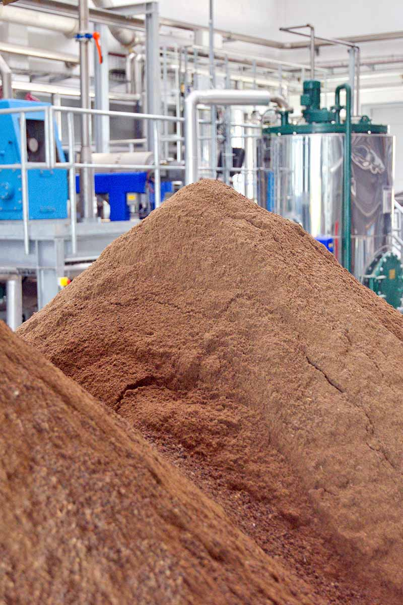 A bone meal production facility with machinery and pipes in the background, and two large mounds of brown bone meal fertilizer in the foreground.