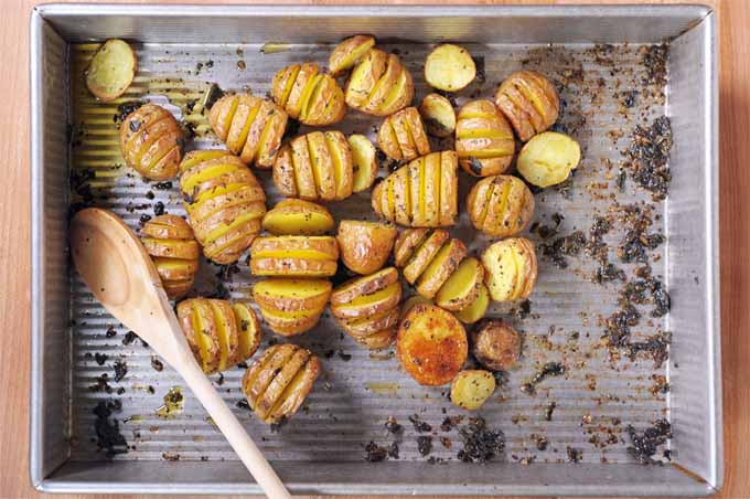 Top down view of roasted sage hasselback potatoes in an aluminum baking pan.